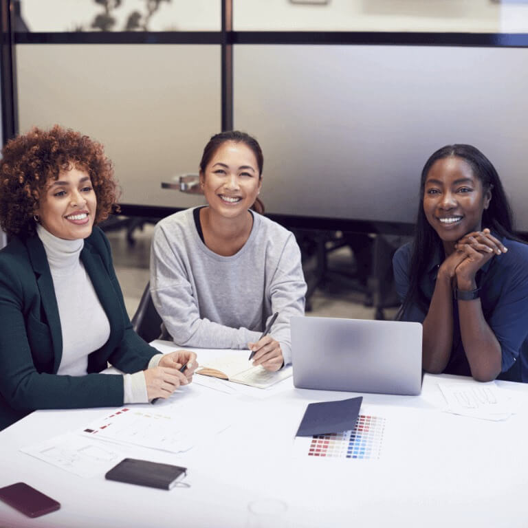 Três mulheres em uma mesa de reunião sorrindo enquanto conversam