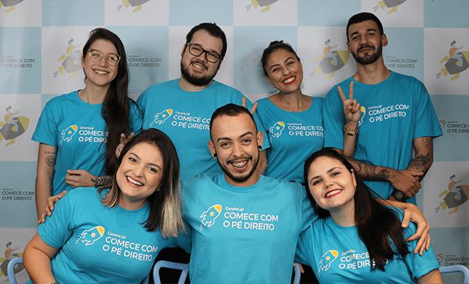 Quatro colaboradores da Comece com o Pé Direito, vestindo uma camiseta azul da empresa