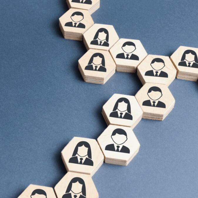 Pequenas peças de madeira com forma de hexágono com desenho de homens e mulheres
